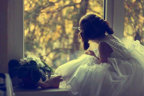 nena vestida de princesa mira por la ventana