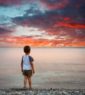 Little boy on beach at sunset