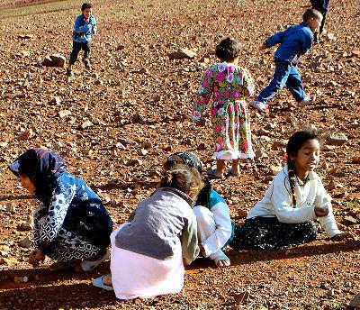 Niñas lanando y atrapando 5 piedras y niños corriendo alrededor. Pueblo Lahfart, Región Sidi Ifni, Marruecos, 2005